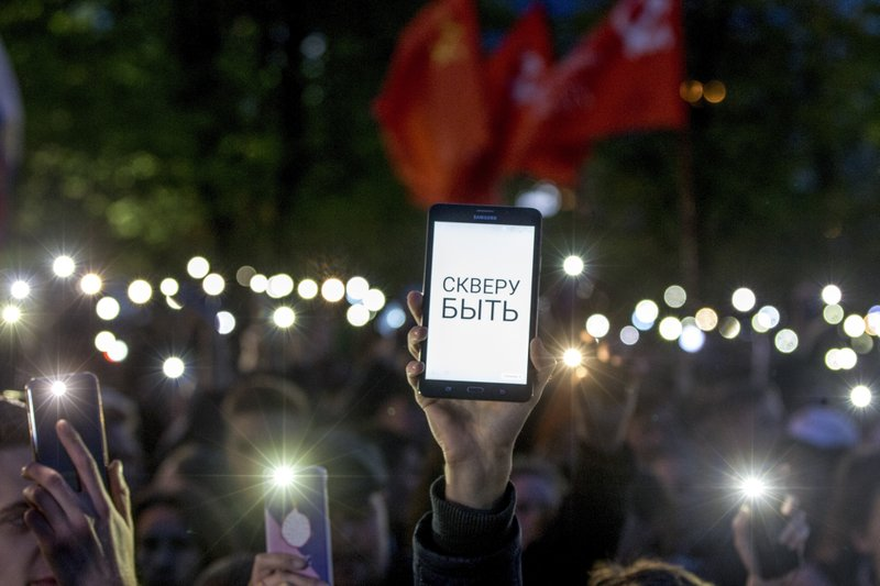 Demonstrators wave their cell phones, with the words on one of them reading
