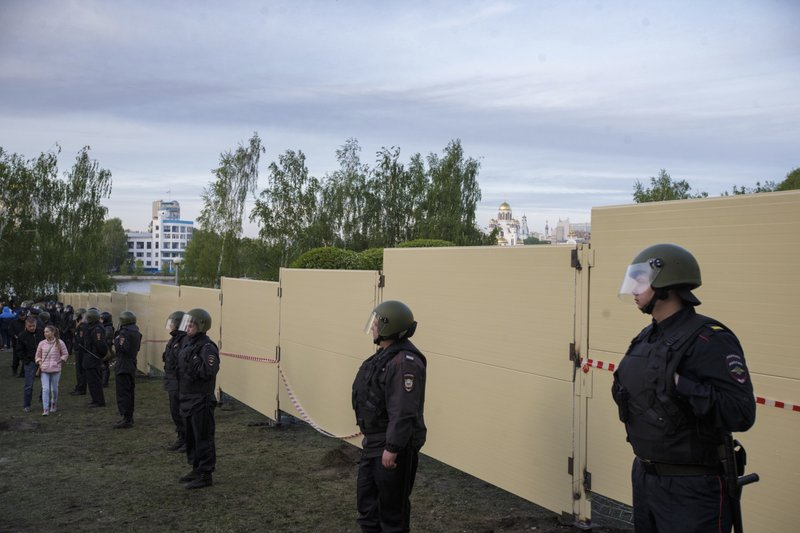 Police officers stand in front of a new built fence during a protest against plans to construct a cathedral in a park in Yekaterinburg, Russia, Wednesday, May 15, 2019. (AP Photo/Anton Basanayev)