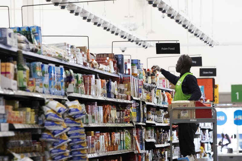 FILE - In this April 24, 2019, file photo a Walmart associate arranges items on a shelf at a Walmart Neighborhood Market in Levittown, N. (AP Photo/Mark Lennihan, File)