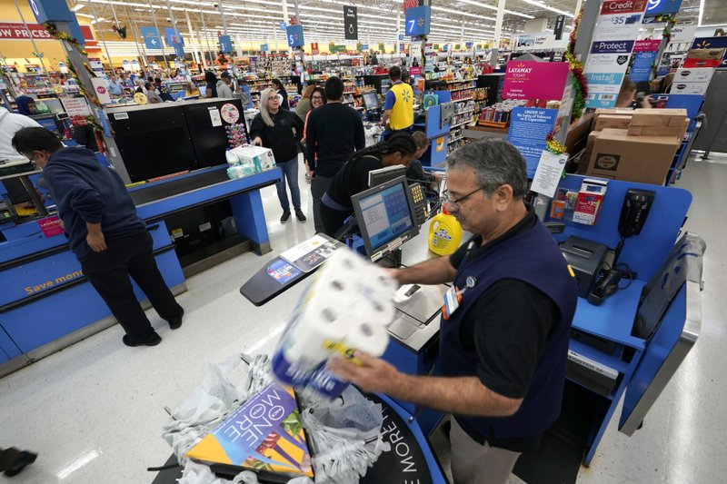 FILE - In this Nov. 9, 2018, file photo Walmart associate Javaid Vohar, right, checks out customers at a Walmart Supercenter in Houston. (AP Photo/David J. Phillip, File)