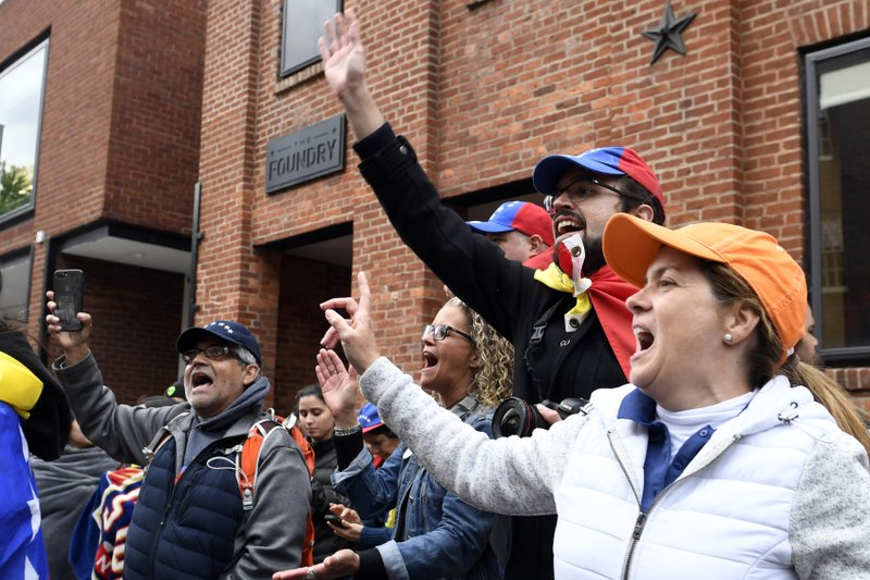 Protester Andres Miguel Harris, second from right, who was born in Venezuela, protests with others outside the Venezuelan embassy in Washington, Tuesday, May 14, 2019. (AP Photo/Susan Walsh)