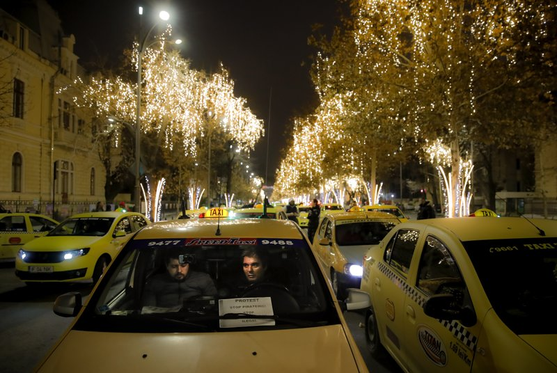 FILE - In this Monday, Jan. 21, 2019, file photo taxi drivers block a main boulevard during a protest against ride hailing services in Bucharest, Romania. The Romanian government has issued an emergency decree ramping up steep fines for drivers of ride-hailing services like Uber and Taxify. The decree taking effect Thursday, May 16, 2019 fines drivers transporting people in their car without a valid taxi license up to $1,175 (1,050 euros) already from the first offense. (AP Photo/Vadim Ghirda, File)