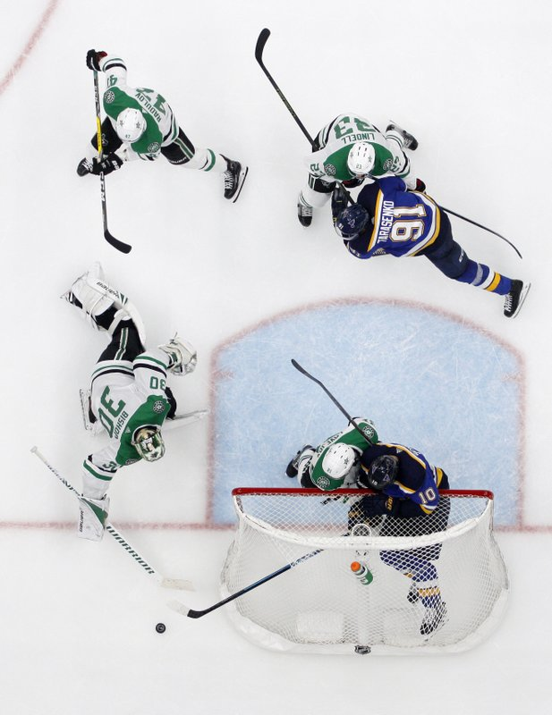 Dallas Stars goaltender Ben Bishop (30) reaches to clear a puck as Alexander Radulov (47), Esa Lindell (23) and Ben Lovejoy, left in net, help against pressure by St. Louis Blues right wing Vladimir Tarasenko (91) and center Brayden Schenn (10) during the third period in Game 7 of an NHL second-round hockey playoff series, Tuesday, May 7, 2019, in St. (AP Photo/Jeff Roberson)