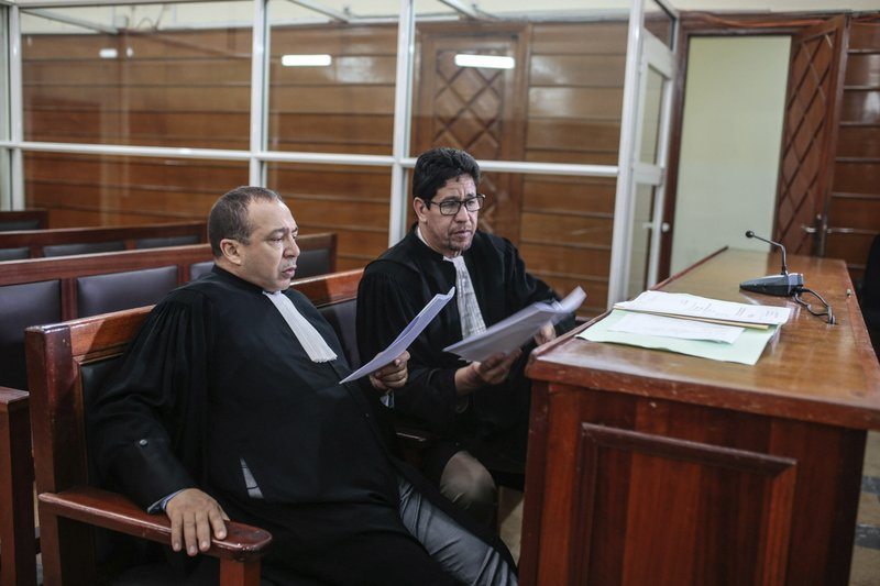 Lawyers read documents inside a court room before the start of a trial session for suspects charged in connection with killing of two Scandinavian tourists in Morocco's Atlas Mountains, in Sale, near Rabat, Morocco, Thursday, May 16, 2019. (AP Photo/Mosa'ab Elshamy)