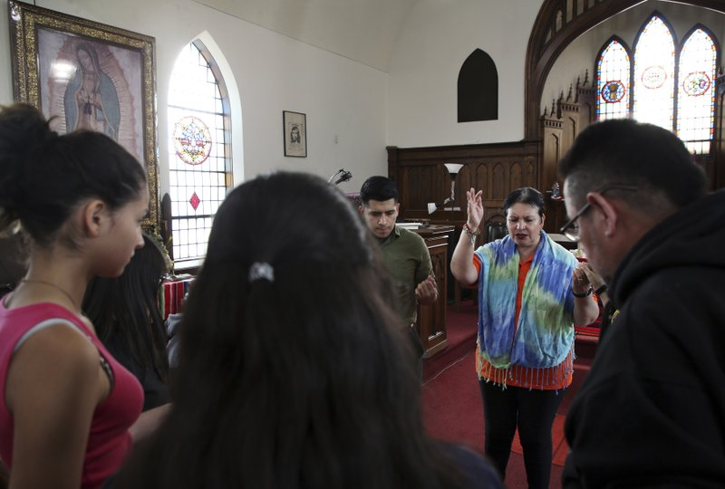 CORRECTS VICTIM'S LAST NAME TO OCHOA-LOPEZ INSTEAD OF OCHOA-URIOSTEGUI  - Pastor Jacobita Cortes offers a prayer at Lincoln United Methodist Church in Chicago on Wednesday, May 15, 2019, for Marlen Ochoa-Lopez, a pregnant teen who was reported missing on April 23, 2019. (Terrence Antonio James/Chicago Tribune via AP)
