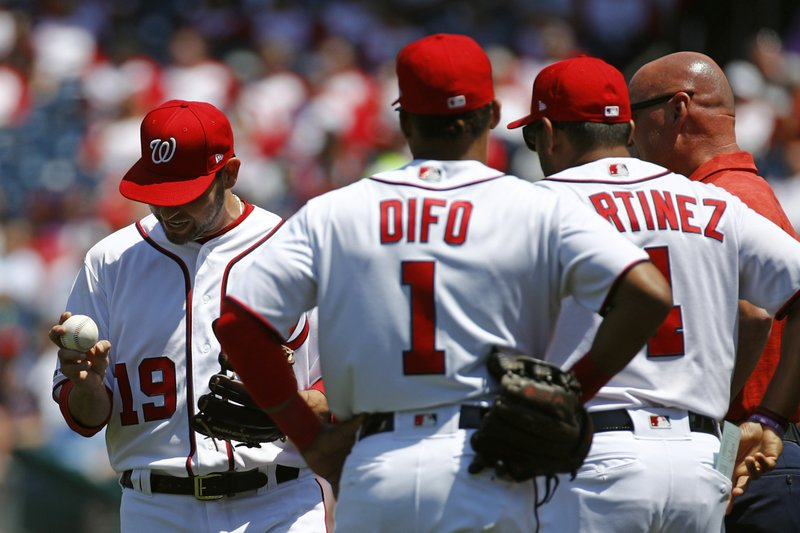 Washington Nationals starting pitcher Anibal Sanchez, left, reacts as he is relieved in the second inning of a baseball game against the New York Mets, Thursday, May 16, 2019, in Washington. Also pictured are shortstop Wilmer Difo (1), manager Dave Martinez (4) and head athletic trainer Paul Lessard. (AP Photo/Patrick Semansky)