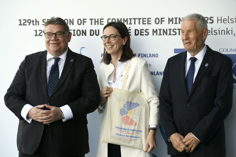 Foreign Minister of Finland Timo Soini, left, and Secretary General of the Council of Europe Thorbjorn Jagland, right, welcomes French Junior Minister for European Affairs Amelie de Montchalin to the Commemoration Ceremony of the 70th anniversary of the Council of Europe in Helsinki, Finland, Thursday May 16, 2019. (Martti Kainulainen/Lehtikuva via AP)