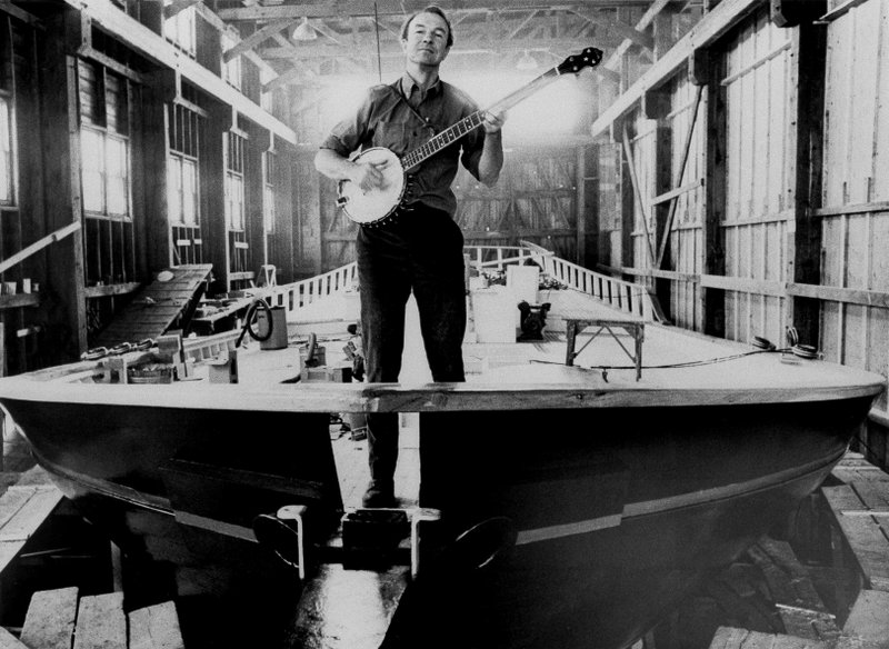 FILE - In this undated file photo, folk singer Pete Seeger strums a banjo on the bow of the 75-foot Hudson River sloop Clearwater to be launched in South Bristol, Maine in May, 1969. (AP Photo, File)