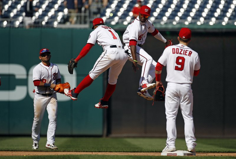 Washington Nationals shortstop Wilmer Difo (1) and center fielder Victor Robles, second from right, celebrate in front of teammates Gerardo Parra, back left, and Brian Dozier after a baseball game against the New York Mets, Thursday, May 16, 2019, in Washington. The Nationals won 7-6. (AP Photo/Patrick Semansky)