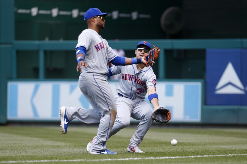 New York Mets right fielder Michael Conforto, right, collides with second baseman Robinson Cano as they fail to catch a fly ball that was hit by Washington Nationals' Howie Kendrick in the fifth inning of a baseball game, Thursday, May 16, 2019, in Washington. (AP Photo/Patrick Semansky)