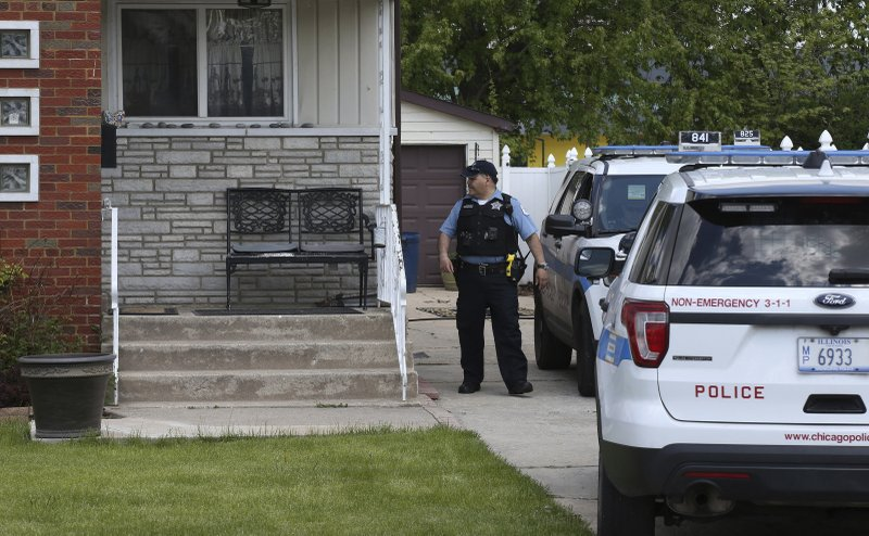 CORRECTS VICTIM'S LAST NAME TO OCHOA-LOPEZ INSTEAD OF OCHOA-URIOSTEGUI - Chicago police watch over a home in Chicago, Wednesday, May 15, 2019, where Marlen Ochoa-Lopez was found strangled and her baby cut from her womb. (Terrence Antonio James/Chicago Tribune via AP)