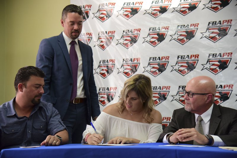 First baseman and member of the National Women's Baseball Team, Diamilette Quiles Alicea, center, signs with The Utuado Highlanders, one of the teams that participate in the Superior Double A Baseball League, in San Juan, Puerto Rico, Thursday, May 16, 2019. (AP Photo/Carlos Giusti)