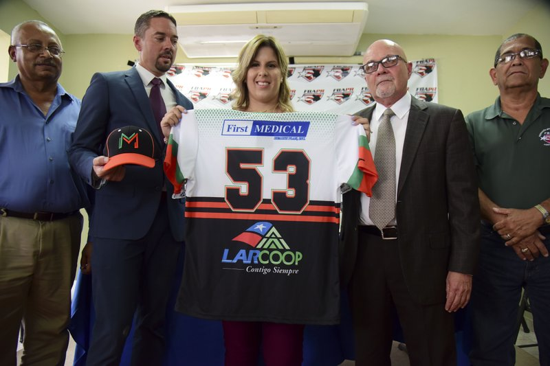First baseman and member of the National Women's Baseball Team, Diamilette Quiles Alicea, center, is presented as the first female player to sign with The Utuado Highlanders, one of the teams that participate in the Superior Double A Baseball League, in San Juan, Puerto Rico, Thursday, May 16, 2019. (AP Photo/Carlos Giusti)