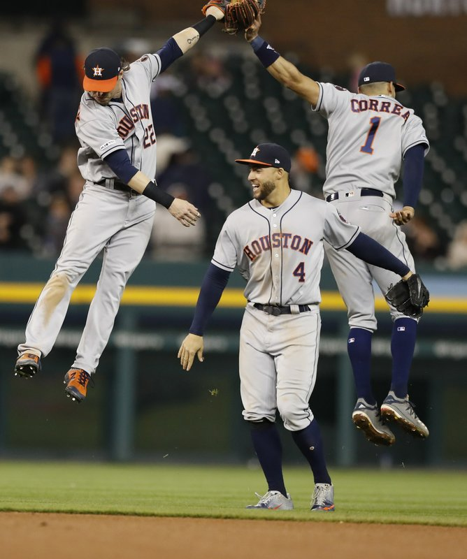 Houston Astros left fielder Josh Reddick (22), right fielder George Springer (4) and shortstop Carlos Correa (1) celebrate the team's 5-1 win over the Detroit Tigers in a baseball game, Wednesday, May 15, 2019, in Detroit. (AP Photo/Carlos Osorio)
