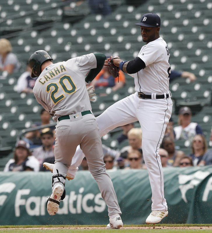 Oakland Athletics' Mark Canha (20) is tagged by Detroit Tigers first baseman Niko Goodrum (28) during the eighth inning of a baseball game, Thursday, May 16, 2019, in Detroit. (AP Photo/Carlos Osorio)