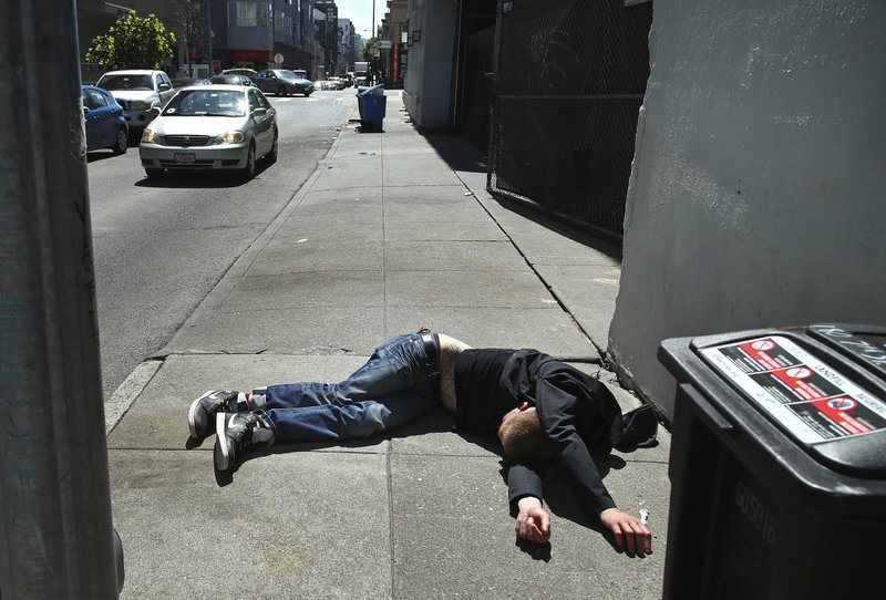 FILE - In this April 26, 2018, file photo, a man lies on the sidewalk beside a recyclable trash bin in San Francisco. (AP Photo/Ben Margot, File)