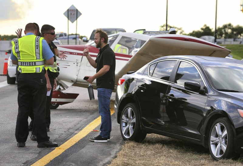 The driver of a black Acura that was struck by a small plane making a crash landing on the eastbound ramp of Maitland Blvd. to Interstate 4, talks to rescue personnel Thursday, May 16, 2019, in Maitland, Fla. (Joe Burbank/Orlando Sentinel via AP)