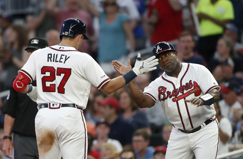 Atlanta Braves rookie Austin Riley (27) celebrates with first base coach Eric Young (2) after driving in a run with a base hit in the third inning of a baseball game against the St. Louis Cardinals Thursday, May 16, 2019, in Atlanta. (AP Photo/John Bazemore)