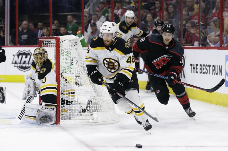 Boston Bruins' Matt Grzelcyk (48) controls the puck against a chasing Carolina Hurricanes' Sebastian Aho (20), of Finland, as Bruins goalie Tuukka Rask (40) guards the net during the second period in Game 4 of the NHL hockey Stanley Cup Eastern Conference finals in Raleigh, N.C., Thursday, May 16, 2019. (AP Photo/Gerry Broome)