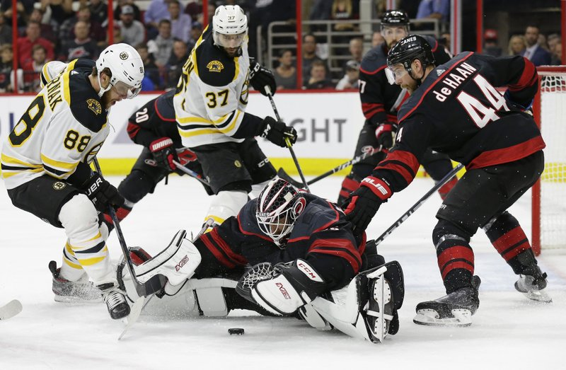 Boston Bruins' David Pastrnak (88), of the Czech Republic, and Patrice Bergeron (37) look to score on Carolina Hurricanes goalie Curtis McElhinney while Hurricanes' Calvin de Haan (44) defends during the first period in Game 4 of the NHL hockey Stanley Cup Eastern Conference final series in Raleigh, N.C., Thursday, May 16, 2019. (AP Photo/Gerry Broome)