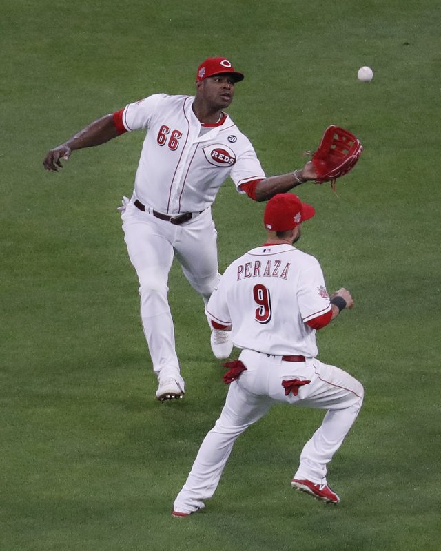 Cincinnati Reds right fielder Yasiel Puig (66) catches a fly ball by Chicago Cubs' Jose Quintana for an out, next to second baseman Jose Peraza during the fifth inning of a baseball game Thursday, May 16, 2019, in Cincinnati. (AP Photo/John Minchillo)