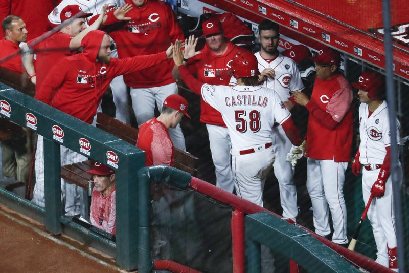 Cincinnati Reds' Luis Castillo (58) celebrates in the dugout after scoring on a wild pitch by Chicago Cubs starting pitcher Jose Quintana during the fifth inning of a baseball game Thursday, May 16, 2019, in Cincinnati. (AP Photo/John Minchillo)