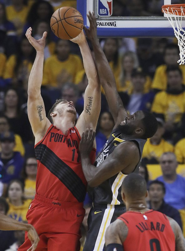 Golden State Warriors forward Draymond Green, top right, defends a shot by Portland Trail Blazers forward Meyers Leonard during the first half of Game 2 of the NBA basketball playoffs Western Conference finals in Oakland, Calif., Thursday, May 16, 2019. (AP Photo/Jeff Chiu)