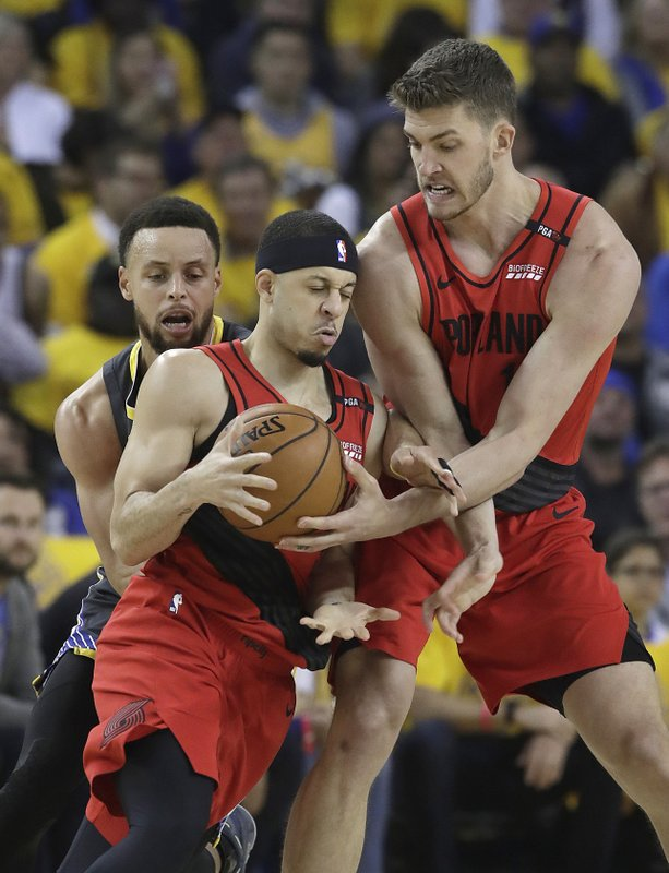 Portland Trail Blazers guard Seth Curry, center, controls the ball next to forward Meyers Leonard, right, as he is is defended by Golden State Warriors guard Stephen Curry during the first half of Game 2 of the NBA basketball playoffs Western Conference finals in Oakland, Calif., Thursday, May 16, 2019. (AP Photo/Jeff Chiu)