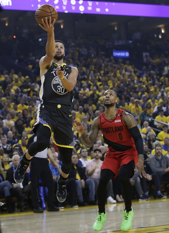 Golden State Warriors guard Stephen Curry (30) shoots next to Portland Trail Blazers guard Damian Lillard (0) during the first half of Game 2 of the NBA basketball playoffs Western Conference finals in Oakland, Calif., Thursday, May 16, 2019. (AP Photo/Jeff Chiu)