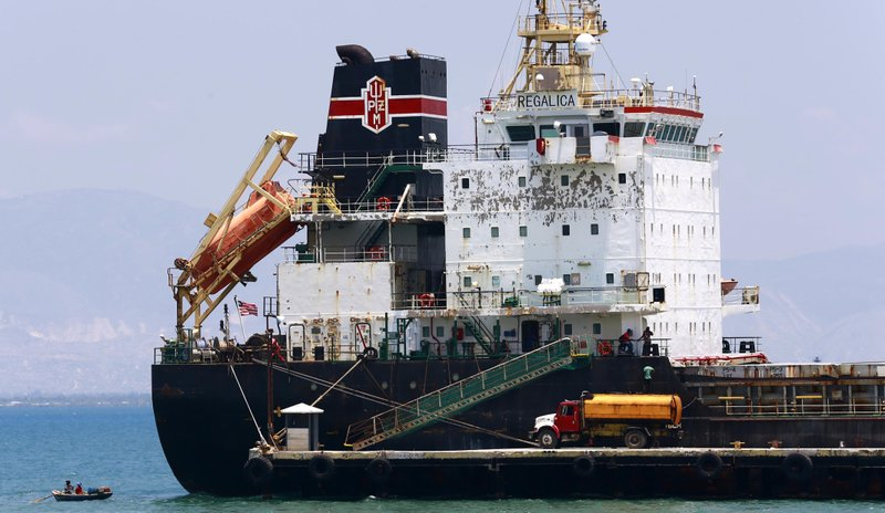 In this April 16, 2019 photo, a ship fills up on fuel from a tanker truck on the Thor terminal in Carrefour, a district of Port-au-Prince Haiti. Through the Venezuelan aid program known as Petrocaribe, more than half the costs of the oil given to Haiti, which came at a heavily discounted price, were repayable over 25 years at a 1% interest rate, allowing the central government to supposedly use the windfall for economic development. (AP Photo/Dieu Nalio Chery) (AP Photo/Dieu Nalio Chery)