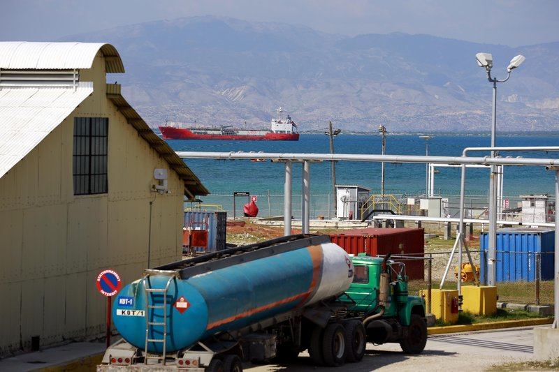 In this April 16, 2019 photo, a tanker truck waits to fill up at the Thor terminal where a ship loaded with fuel awaits to unload its cargo in Carrefour, a district of Port-au-Prince, Haiti. Through the Venezuelan aid program known as Petrocaribe, Haiti once received roughly 60,000 barrels of oil a day under favorable terms that beat anything on the open market. (AP Photo/Dieu Nalio Chery)