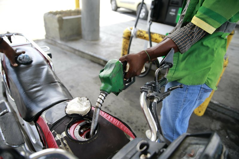 In this April 16, 2019 photo, a gas station attendant fills the gas tank of a motorcycle in Port-au-Prince, Haiti. Through the Venezuelan aid program known as Petrocaribe, more than half the costs of the oil given to Haiti, which came at a heavily discounted price, were repayable over 25 years at a 1% interest rate, allowing the central government to supposedly use the windfall for economic development. (AP Photo/Dieu Nalio Chery)