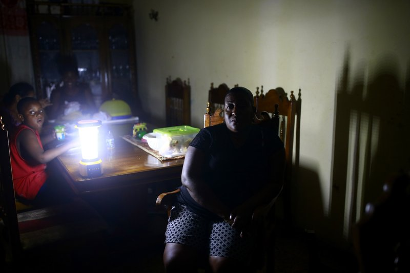 In the April 17, 2019 photo, Jennifer Jean sits with her family in the living room of her home, lit only by camping lantern, in Port-au-Prince, Haiti. Since the blackouts started Jean's fledgeling catering business has cratered, making it impossible to do basic activities. Without refrigeration, she now has to buy ice on the street to keep her prepared food cool.
