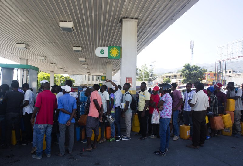 In this April 10, 2019 photo, people line up at a gas station to fill containers with fuel, in Port-au-Prince, Haiti. As Venezuelan President Nicolás Maduro's government has struggled with plunging petroleum production and a cratering economy, the South American country has been forced to stop sending billions in subsidized oil to countries throughout Central America and the Caribbean, including Haiti. (AP Photo/Dieu Nalio Chery)