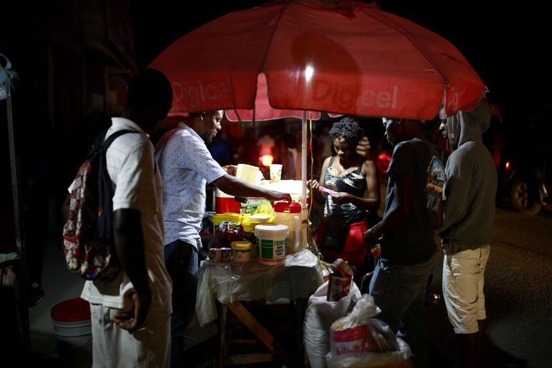 In this April 16, 2019 photo, street vendors sell juice in Petion-Ville, Haiti. The current fuel crisis is helping push Haiti's economy dangerously close to recession. (AP Photo/Dieu Nalio Chery)