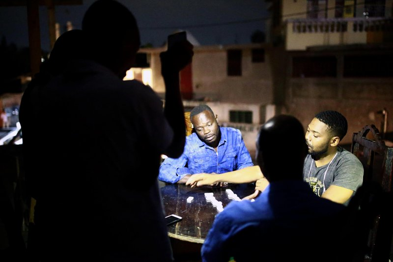 In this April 16, 2019 photo, a man holds up his mobile phone to light others playing dominos in Petion-Ville, Haiti. Nighttime activity has ground to a halt as armed robbers hold up street merchants or break into people's homes in darkness. (AP Photo/Dieu Nalio Chery)
