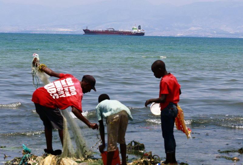 In this April 16, 2019 photo, residents fish while a tanker waits out in the bay to unload its cargo at the Thor terminal in Carrefour, a district of Port-au-Prince, Haiti. The current fuel crisis is helping push Haiti's economy dangerously close to recession. (AP Photo/Dieu Nalio Chery)