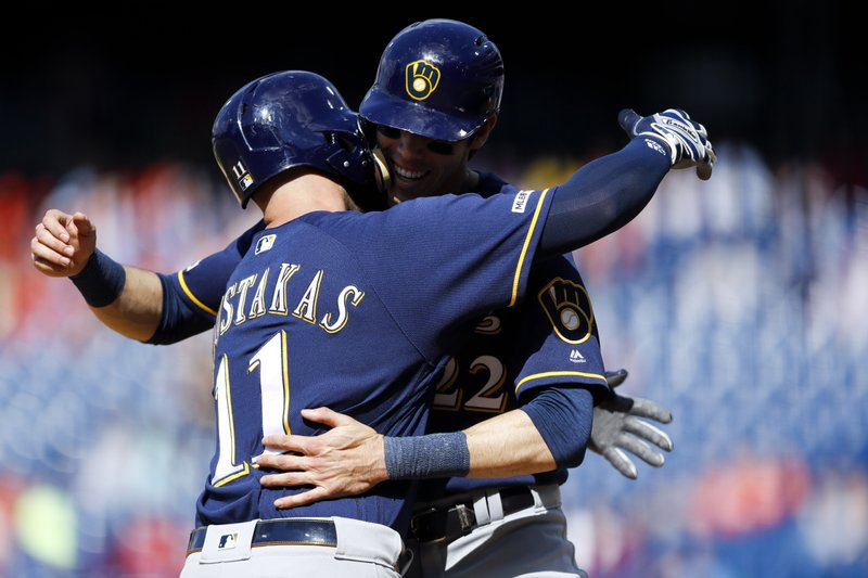 Milwaukee Brewers' Mike Moustakas, left, and Christian Yelich celebrate after Moustakas' two-run home run off Philadelphia Phillies relief pitcher Austin Davis during the ninth inning of a baseball game, Thursday, May 16, 2019, in Philadelphia. Milwaukee won 11-3. (AP Photo/Matt Slocum)