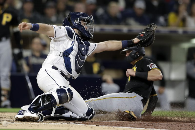 San Diego Padres catcher Austin Hedges is late with the tag as Pittsburgh Pirates' Kevin Newman scores from third during the fifth inning of a baseball game Thursday, May 16, 2019, in San Diego. (AP Photo/Gregory Bull)