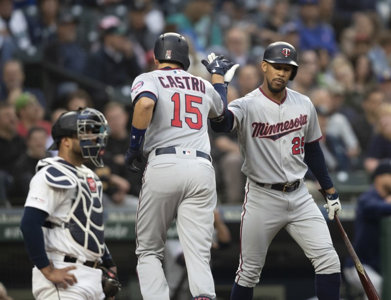 Minnesota Twins' Jason Castro (15) is congratulated by Byron Buxton after hitting a solo home run off of Seattle Mariners starting pitcher Erik Swanson during the second inning of a baseball game Thursday, May 16, 2019, in Seattle. (AP Photo/Stephen Brashear)
