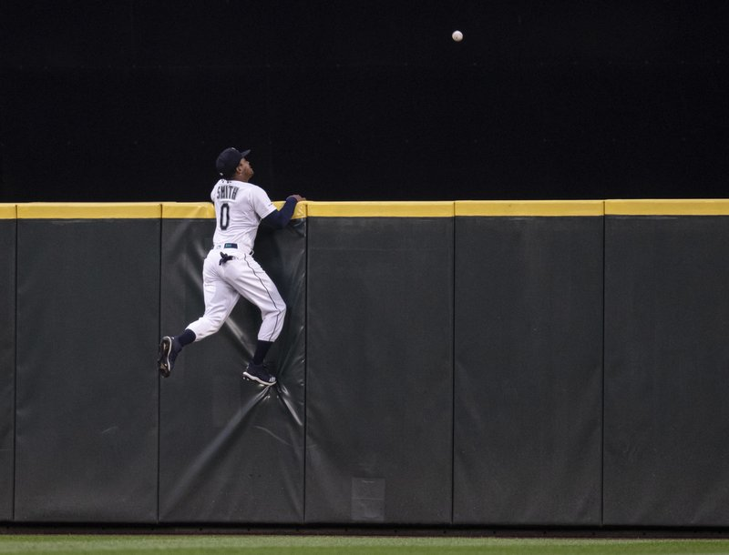 Seattle Mariners center fielder Mallex Smith climbs the wall, but can't get to a three-run home run by Minnesota Twins' Byron Buxton off  pitcher Erik Swanson during the fourth inning of a baseball game Thursday, May 16, 2019, in Seattle. (AP Photo/Stephen Brashear)