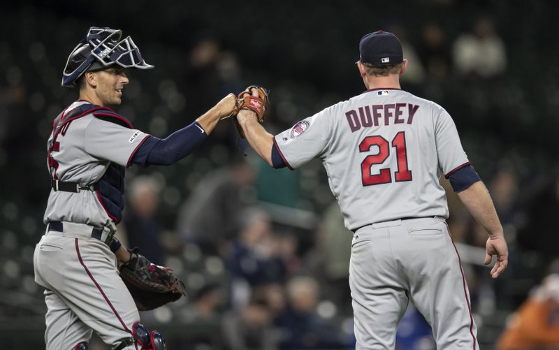 Minnesota Twins catcher Jason Castro, left, and relief pitcher Tyler Duffey celebrate after the team's baseball game against the Seattle Mariners, Thursday, May 16, 2019, in Seattle. The Twins won 11-6. (AP Photo/Stephen Brashear)