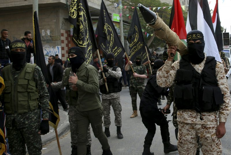 FILE - In this Dec. 22, 2017 file photo, masked members of the Palestinian Al-Quds Brigades, the military wing of the Islamic Jihad group, march with their rifles during a protest against U.S. President Donald Trump's decision to recognize Jerusalem as Israel's capital, in Nusseirat refugee camp, central Gaza Strip. From Lebanon and Syria to Iraq, Yemen, and the Gaza Strip, Iran has significantly expanded its footprint over the past decade, finding and developing powerful allies in conflict-ravaged countries across the Middle East. (AP Photo/Adel Hana, File)