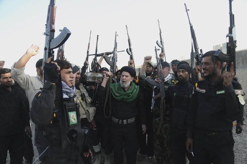 FILE - In this March 14, 2015 file photo, Iraqi Shiite militia group called Imam Ali Brigades chant slogans against the Islamic State group at the battlefield in Tikrit, 130 kilometers (80 miles) north of Baghdad, Iraq. From Lebanon and Syria to Iraq, Yemen, and the Gaza Strip, Iran has significantly expanded its footprint over the past decade, finding and developing powerful allies in conflict-ravaged countries across the Middle East. Iran has trained, financed, and equipped Shiite militias in Iraq that battled U.S. forces in the years after the 2003 invasion and remobilized to battle the Islamic State group a decade later. (AP Photo/Khalid Mohammed, File)