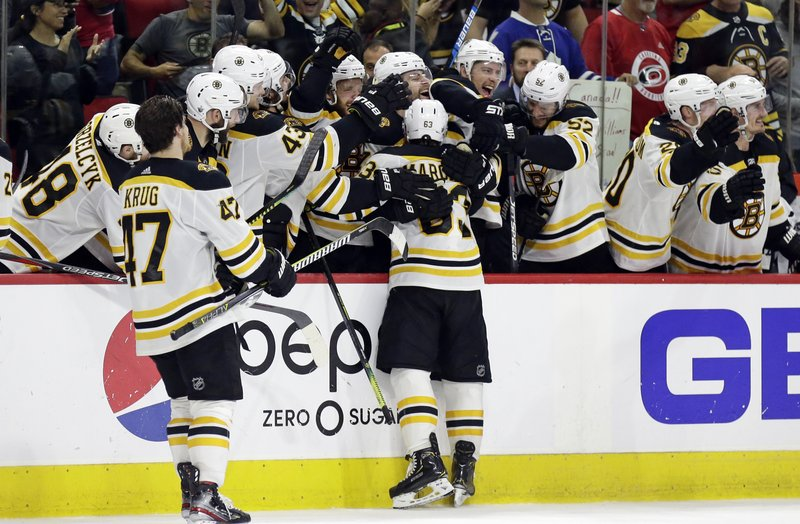 Boston Bruins hug Brad Marchand (63) following Marchand's empty-net goal against the Carolina Hurricanes during the third period in Game 4 of the NHL hockey Stanley Cup Eastern Conference finals in Raleigh, N.C., Thursday, May 16, 2019. Boston won 4-0 to advance to the Stanley Cup Final. (AP Photo/Gerry Broome)