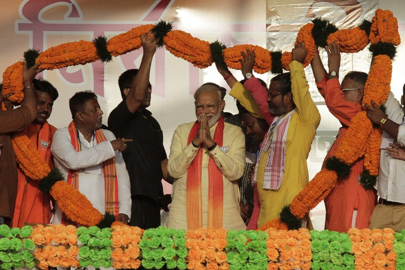 FILE- In this Thursday, May 16, 2019 file photo, Indian Prime Minister Narendra Modi, center, is offered a giant floral garland during an election rally in Mathurapur, south of Kolkata, in the eastern Indian state of West Bengal. Modi has taken his Bharatiya Janata Party's fight to the state of West Bengal, where it hopes to retain a majority in staggered general elections concluding this week by diluting the strength of a formidable opponent, chief minister Mamata Banerjee. (AP Photo/Bikas Das, File)