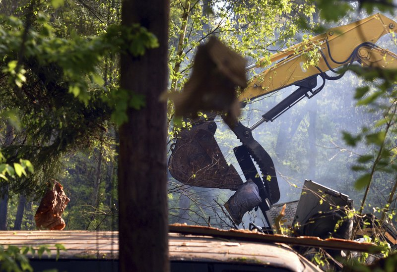 Debris hangs from trees as an excavator moves rubble after a deadly home explosion in Dorrance, Pa., Friday, May 17, 2019. The cause of the blast remains under investigation. (Aimee Dilger/The Times Leader via AP)