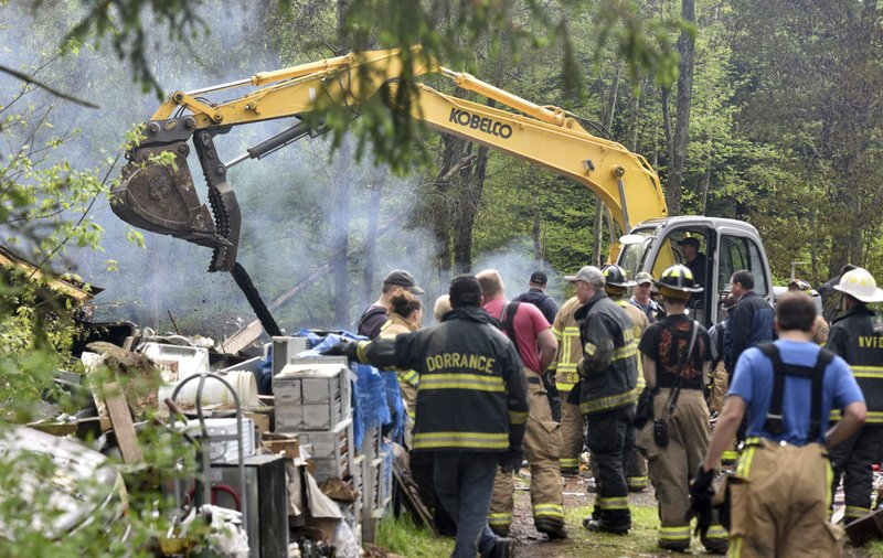 Firefighters watch for a fire to rekindle as an excavator moves rubble to locate a missing man, following a deadly home explosion in Dorrance, Pa., Friday, May 17, 2019. The cause of the blast remains under investigation. (Aimee Dilger/The Times Leader via AP)