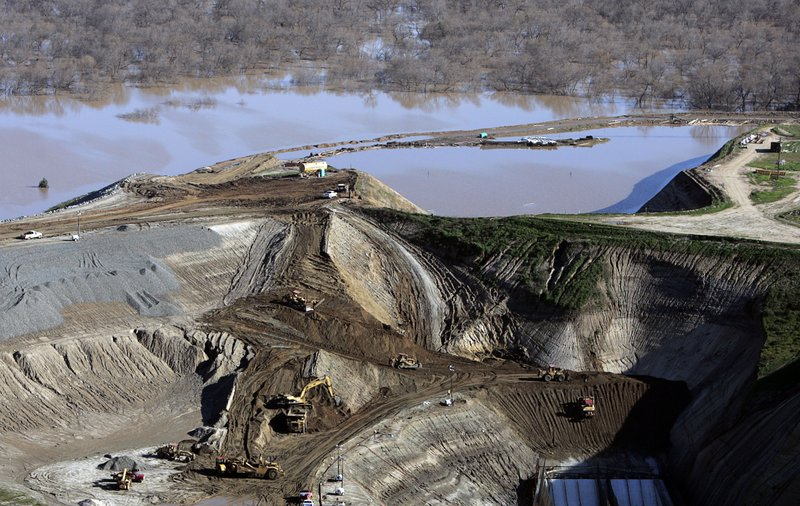 FILE - In this Jan. 14, 2005 file photo crews using heavy machinery wok to stop a leak of excess rainwater from the Prado Dam that forced the evacuation of hundreds of homes in Corona, Calif. The U.S. Army Corps of Engineers says a recent assessment has raised concern about the potential for failure of the spillway of a flood control dam on a Southern California river where 1.4 million people live downstream. The Corps said Thursday, May 16, 2019, that it has changed the risk characterization of Prado Dam from moderate urgency to high urgency. (AP Photo/Chris Carlson, File)