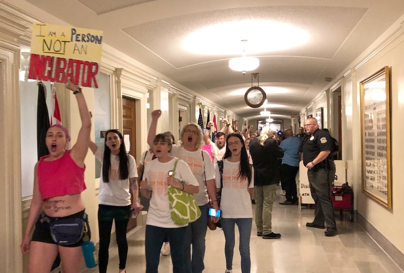 Protesters march through the halls of the Missouri Capitol outside the House chamber on Friday, May 17, 2019, in Jefferson City, Missouri, in opposition to legislation prohibiting abortions at eight weeks of pregnancy. Missouri's Republican-led Legislature has passed a sweeping bill to ban abortions at eight weeks of pregnancy, and Republican Gov. Mike Parson is expected to sign it. The House approved the measure Friday May 17, 2019. (AP Photo/David A. Lieb)